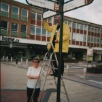 Mrs Norman supports husband Derek as he amends an illegal metric sign in Crawley, Sussex.